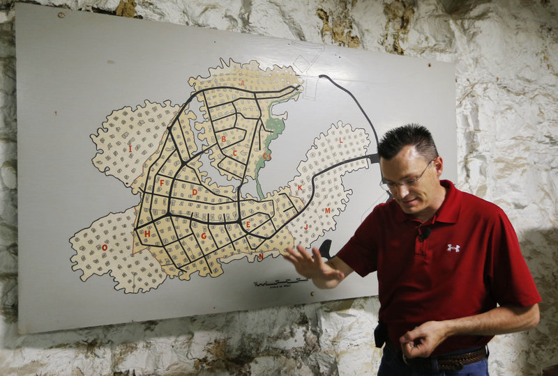 Missouri investor Coby Cullins stands next to a map of the Vivos Survival Shelter and Resort during a tour of the underground facility in Atchison, Kan., earlier this week.