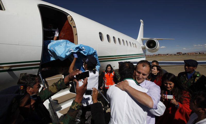U.S. Dr. Joseph Currier, right, facing camera, embraces a Bolivian doctor, as a stretcher carrying four-year-old Rosalie is placed into a private plane at the airport in El Alto, Bolivia, Thursday, June 20, 2013. Rosalie, who was attacked by a Rottweiler about 4 months ago, came out of her coma and is being transferred to a hospital in Boston for reconstructive face surgery. (AP Photo/Juan Karita)