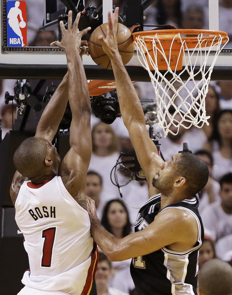 Tim Duncan of the San Antonio Spurs knocks away a shot by Chris Bosh of the Miami Heat – make that the champion Miami Heat – in Game 7 of the NBA finals Thursday night.