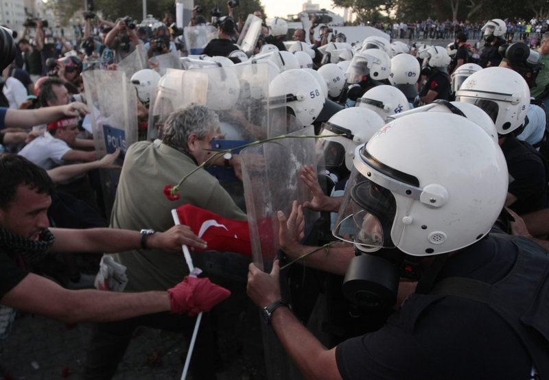 Riot policemen push protesters during clashes at Taksim Square in Istanbul on Saturday. The protesters were honoring the memory of four people killed in previous protests.