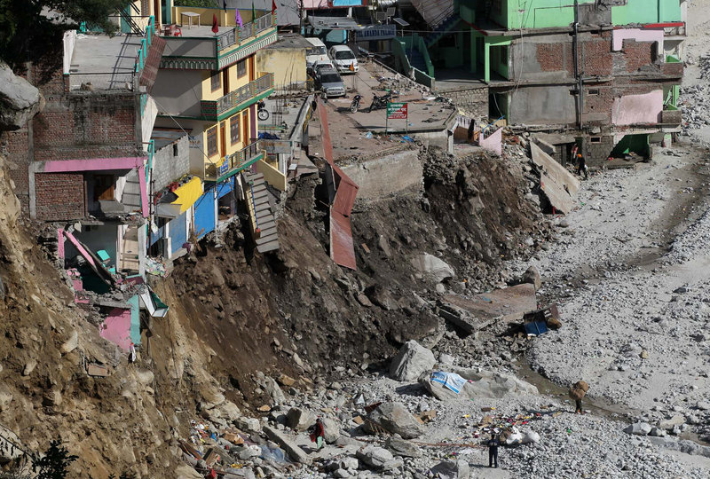 Buildings teeter at the edge of an area eroded by floods and landslides in Govindghat, India. Soldiers were working Saturday to evacuate tens of thousands of people in northern India's Himalayas, building bridges and opening routes.