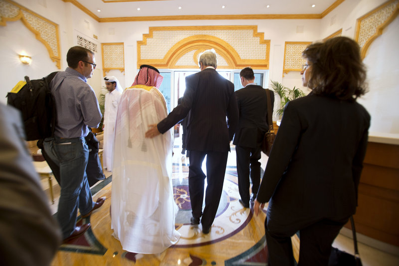 Secretary of State John Kerry walks through the airport after being greeted on arrival in Doha, Qatar, on Saturday for the beginning of peace talks with the Taliban.