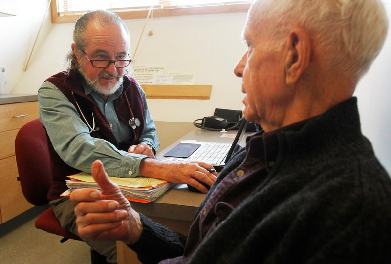 Ronald Pitkin, right, meets with his doctor, John Matthew, in Plainfield, Vt.