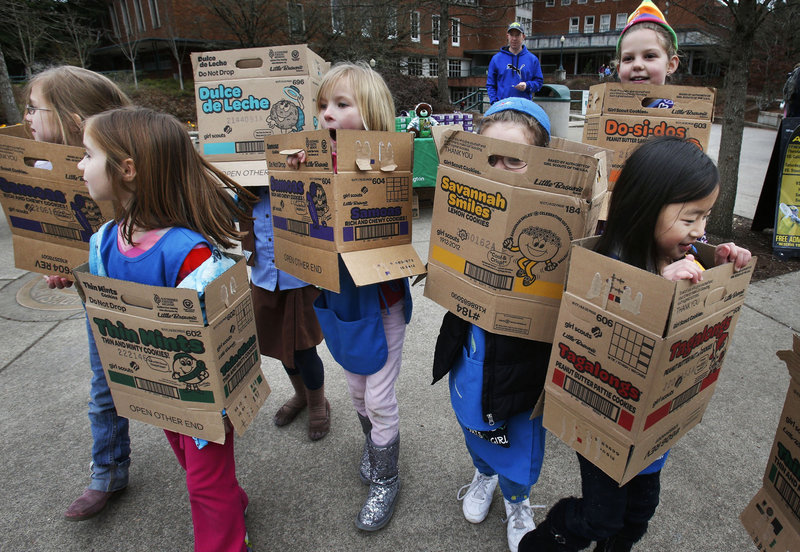 Wrapped in boxes emptied from earlier cookie sales, Girl Scouts from Troop 20337 in Eugene, Ore., fan out on the University of Oregon campus in search of more cookie customers. One year after the organization celebrated its 100th anniversary, even the proceeds of cookie sales are being questioned as to what they support.