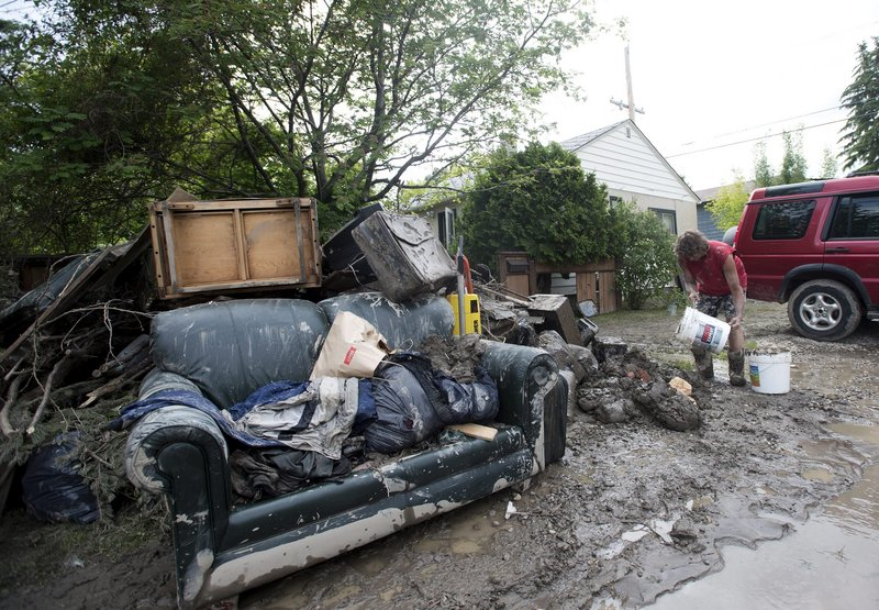Residents are in flood clean-up mode in Calgary, Alberta, on Monday. Alberta's premier pledged $1 billion to help people recover from floods that devastated parts of the province.
