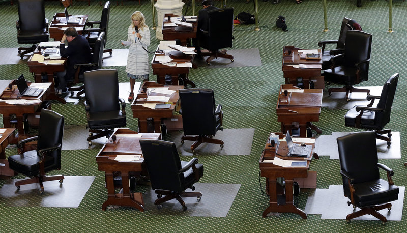 Wendy Davis, D-Fort Worth, stands on a near-empty floor as she filibusters in an effort to kill an abortion bill Tuesday in Austin, Texas. The bill would ban abortion after 20 weeks of pregnancy and force many clinics to close.