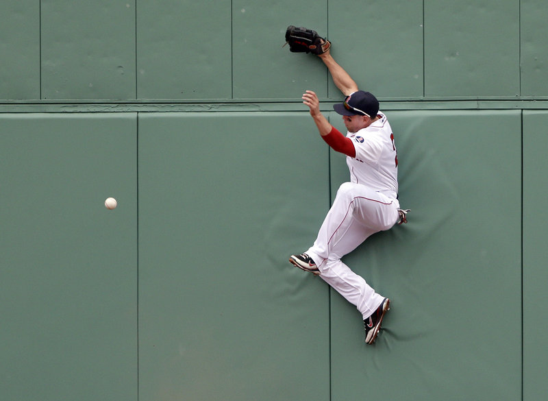 Boston center fielder Jacoby Ellsbury jumps against the wall but cannot catch Todd Helton's drive, which went for a double in the top of the fourth inning.