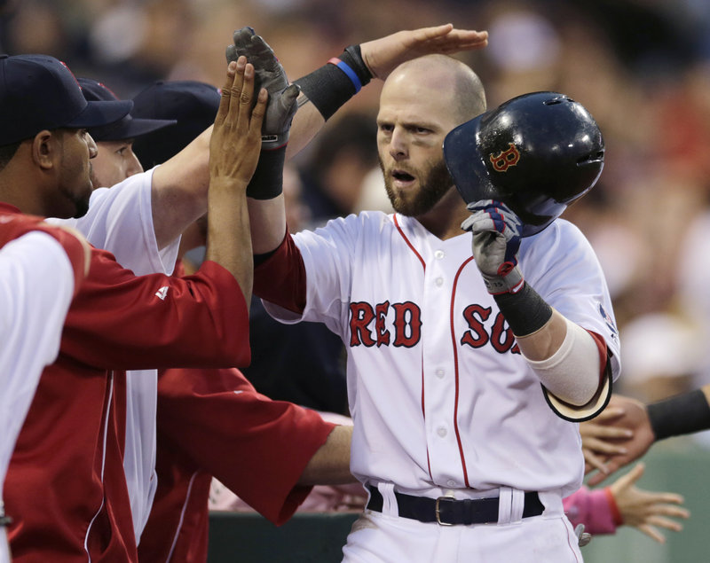 Dustin Pedroia heads to the dugout to a big welcome from his teammates after his two-run homer highlighted a seven-run second inning that gave the Red Sox all they would need to take Thursday's opening game against the Toronto Blue Jays at Fenway Park.