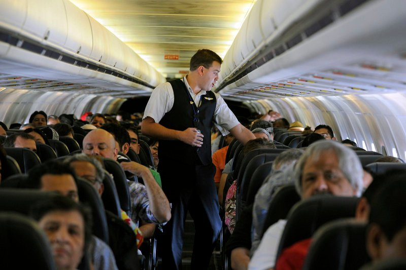 Allegiant Air flight attendant Chris Killian prepares passengers for the flight from Las Vegas to Laredo, Texas. The airline has low fares but tacks on many fees.