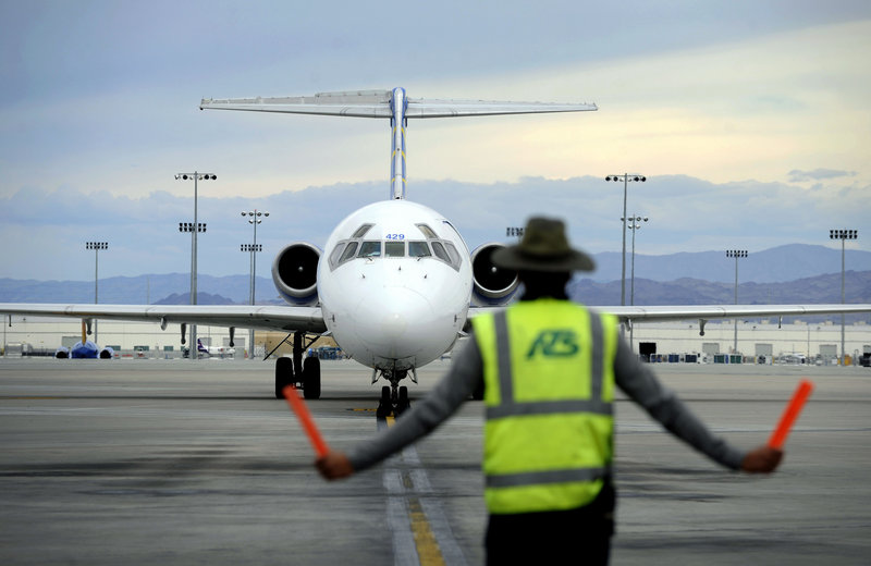 A ground worker guides an incoming Allegiant Air jet at McCarran International Airport in Las Vegas. Allegiant promotes its destinations, rather than itself, to those who seldom fly.