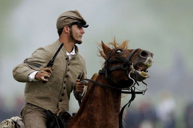 A mounted Confederate re-enactor takes part in a demonstration of a battle commemorating the 150th anniversary of the Battle of Gettysburg on Friday.