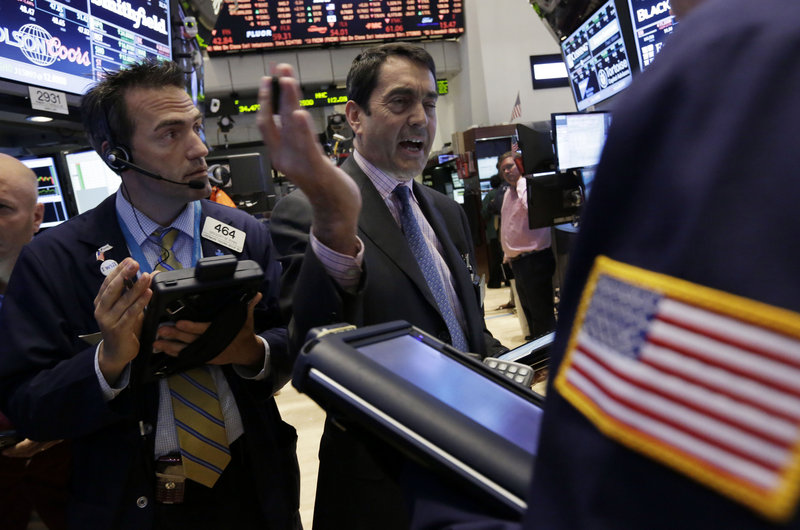 Gregory Rowe, left, and Mark Muller work on the on the floor of the New York Stock Exchange at the close of trading, Friday.