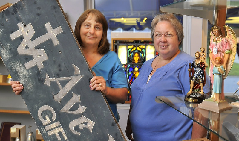 On Friday, Ave Maria Gift Shop owner, Connie Somma, left, and longtime employee Joanne Costa are surrounded by some of the store's iconic merchandise and the sign they took down today. The shop is closing after 65 years.