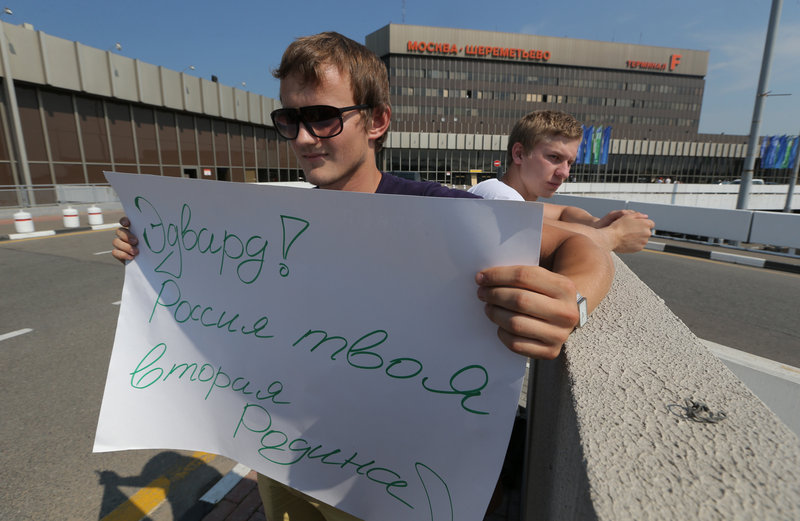 "A supporter of National Security Agency leaker Edward Snowden holds a poster Friday outside Sheremetyevo airport in Moscow, where Snowden is believed to remain at the transit zone. The poster reads: ""Edward! Russia is your second Motherland!"""