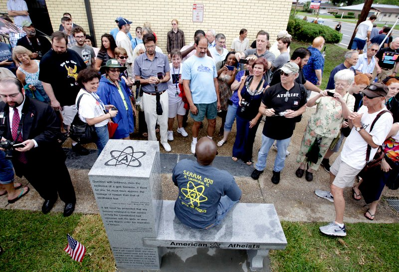 People gather around to sit and take photos during the unveiling of an atheist monument outside the Bradford County Courthouse on Saturday in Stark, Fla.