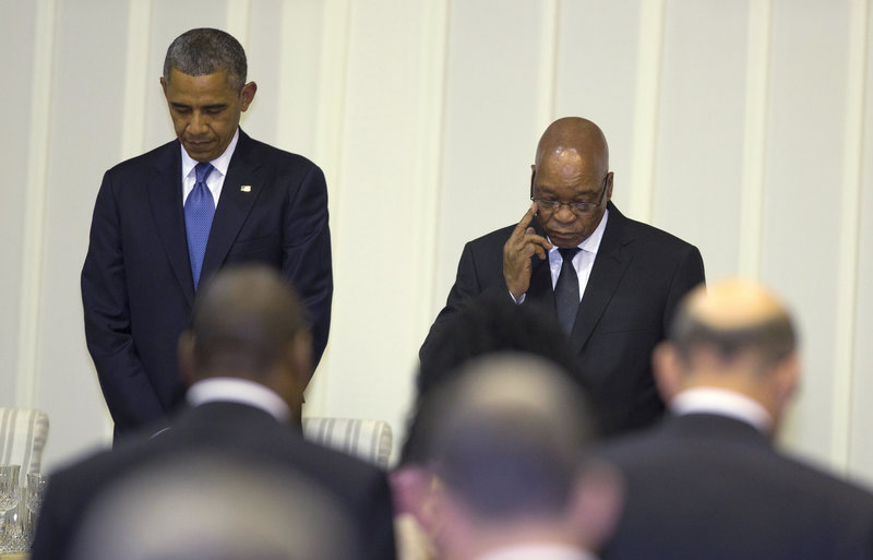 President Obama observes a moment of silence for Nelson Mandela on Saturday at a dinner in Pretoria.