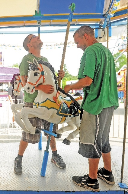 Adam Trott, 25, left, and Tim Siwek, 32, install a horse on one of the company's merry-go-rounds Tuesday in Fairfield.
