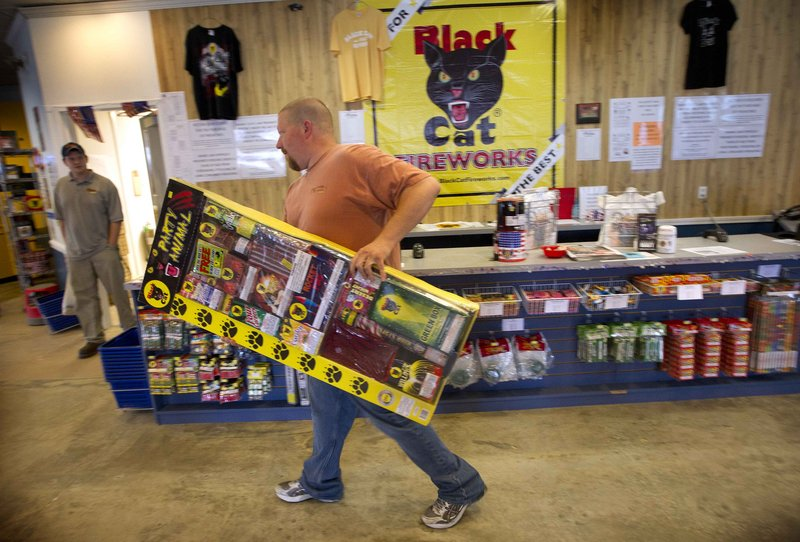 Pyro City Maine worker Zach Gushing carries a jumbo box of aerial and ground fireworks Friday at the Winslow retail store.