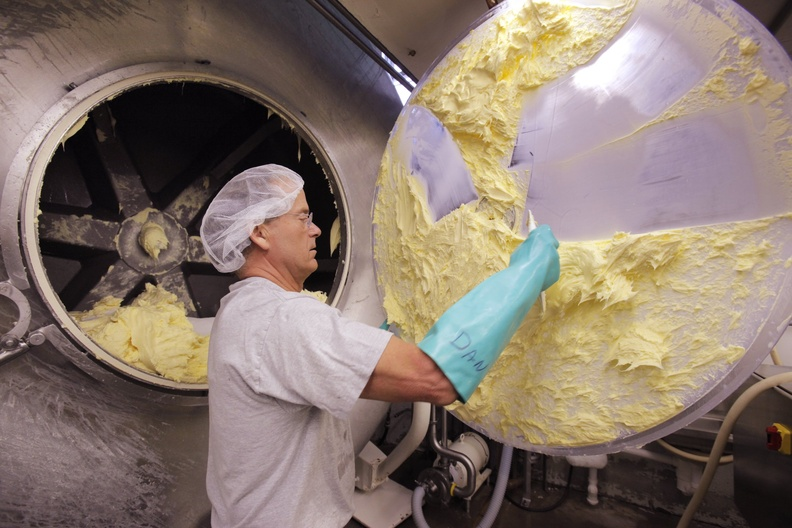 Daniel Patry scrapes butter off the door to a mixer at Kate's Homemade Butter in Old Orchard Beach in 2011. The butter gets a mention in a new Adam Sandler comedy.