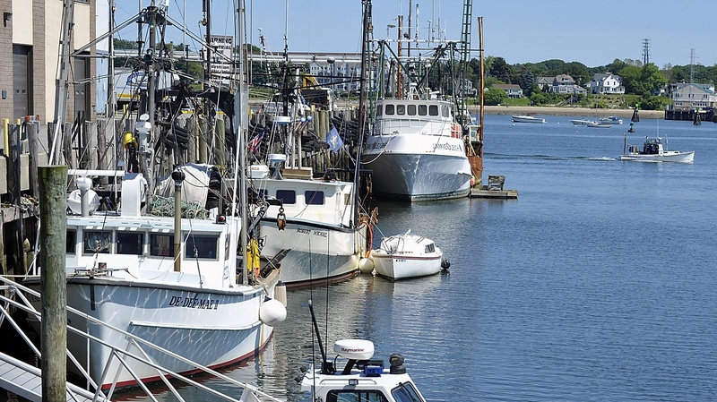 A lobster boat passes by fishing boats in Portland.