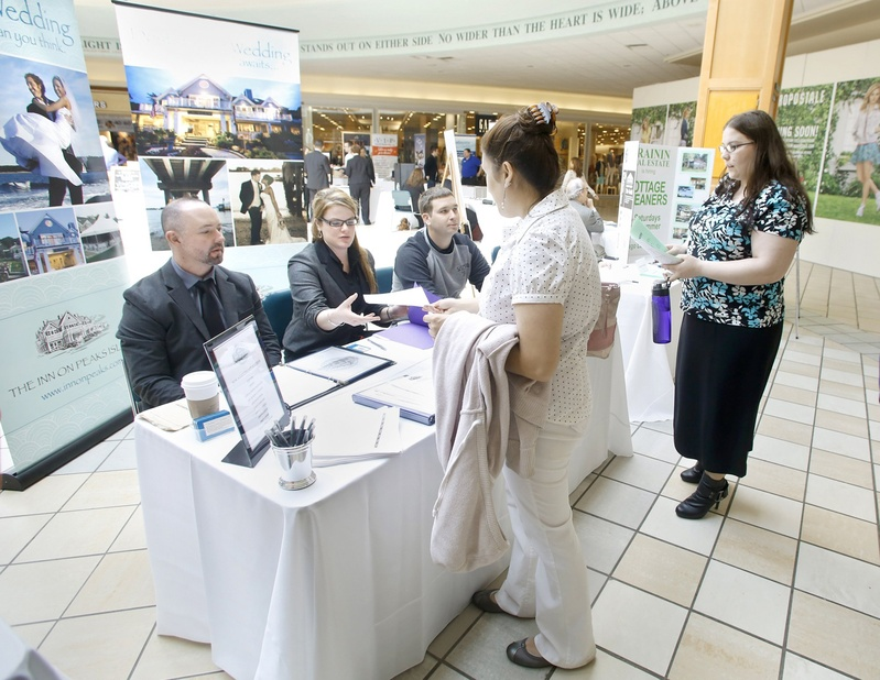 Job seekers collect information at a Hospitality Job Fair at the Maine Mall in April. The U.S. Bureau of Labor Statistics estimates that the number of unemployed people in Maine is down 3,300 from last year.