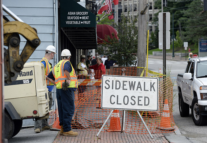 Workers look over a damaged sidewalk on Congress Street after a water main break Monday.