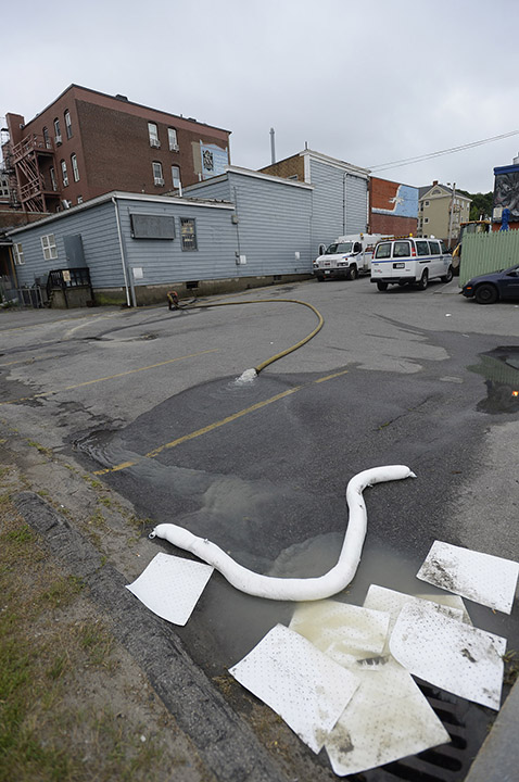 Water is pumped from a building after a water main break on Congress Street in Portland on Monday.