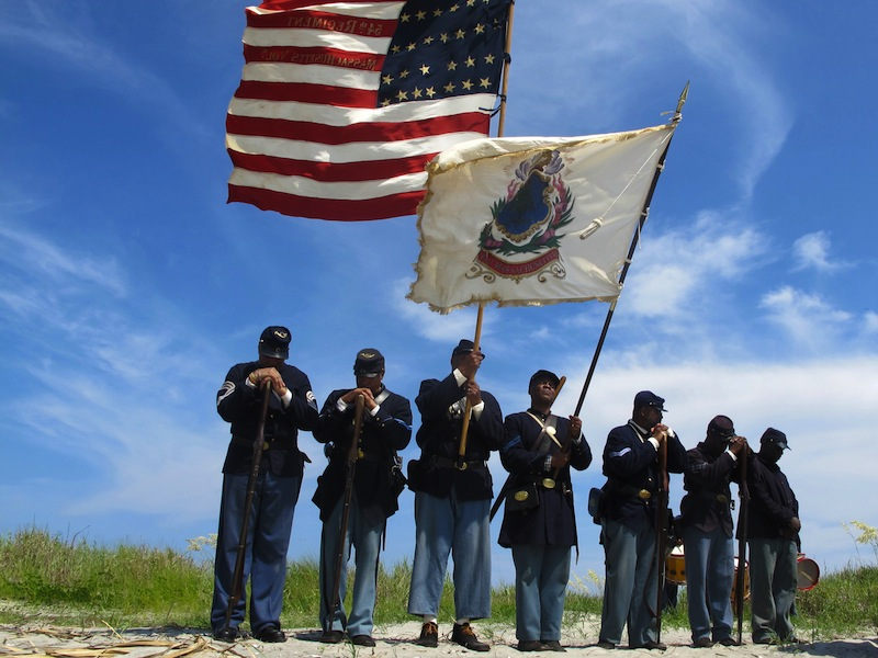 """Black re-enactors in a color guard pray on Morris Island near Charleston, S.C., on Thursday, July 18, 2013 during a observance of the 150th anniversary of the charge of the black 54th Massachusetts Volunteer Infantry in a fight commemorated in the film """"Glory."""" (AP Photo/Bruce Smith)"""