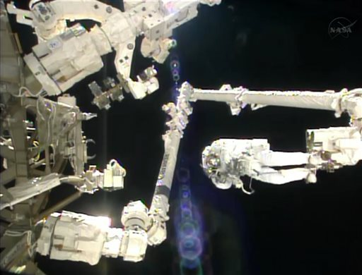 In this image made from video provided by NASA, Italian astronaut Luca Parmitano stands on the end of a robotic arm during a spacewalk outside the International Space Station on Tuesday, July 9, 2013.