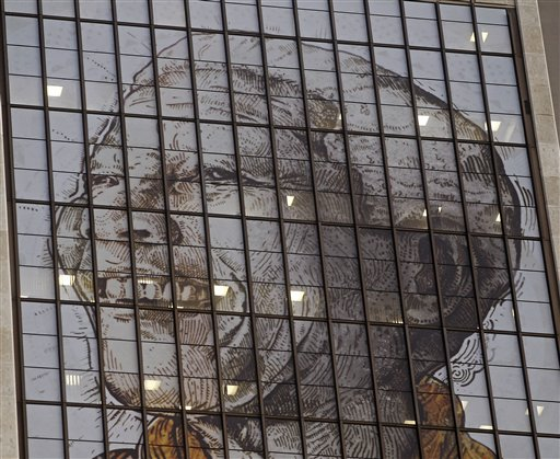 A portrait representing former South African President Nelson Mandela is displayed on the windows of a building as lights inside the building reflect in downtown Cape Town, South Africa on Thursday.