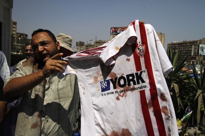 A supporter of ousted Egyptian President Mohammed Morsi stands outside a local hospital in Cairo holding a bloodied shirt he says belongs to a protester shot by soldiers during a demonstration, Monday, July 8, 2013. Egyptian soldiers and police opened fire on supporters of the ousted president early Monday in violence that left dozens of people killed, including one officer, outside a military building in Cairo where demonstrators had been holding a sit-in, government officials and witnesses said. (AP Photo/Nasser Shiyoukhi)