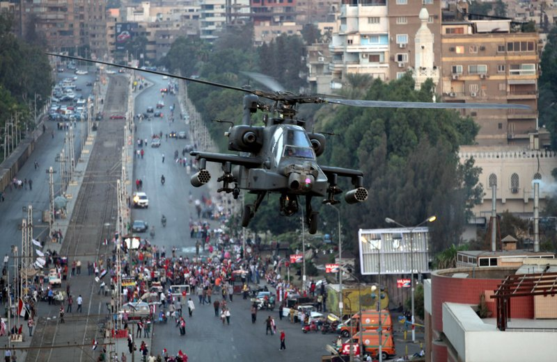 An Egyptian military attack helicopter flies over the presidential palace in Cairo, Egypt, on Friday.