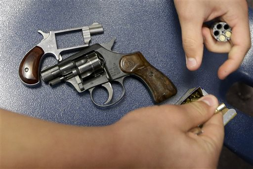 In this July 11, 2013, photo a student loads blank ammunition into one of two starter pistols being used for training exercises at Clarksville High School in Clarksville, Ark.