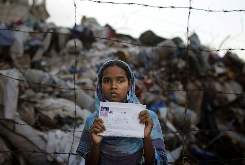 In this June 14, 2013 file photo, Bangladeshi Hashna holds a picture of her sister Josna Khatun, 18 years old, who was a garment worker and is missing following the collapse of the Rana Plaza building poses next to the rubble in Savar, near Dhaka, Bangladesh. A group of 17 U.S. retailers and clothing makers have agreed to a five-year safety pact aimed at improving conditions after the deadliest disaster in the history of the garment industry killed more than 1,100 people. (AP Photo/Kevin Frayer)