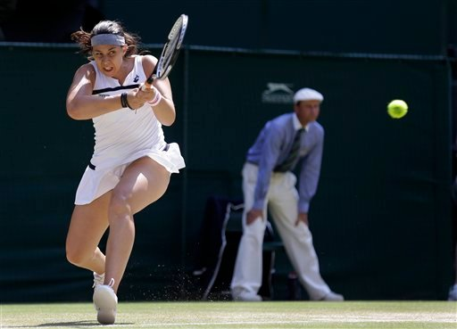 Marion Bartoli of France plays a return to Sabine Lisicki of Germany during their Women's singles final match at the All England Lawn Tennis Championships in Wimbledon, London, Saturday.