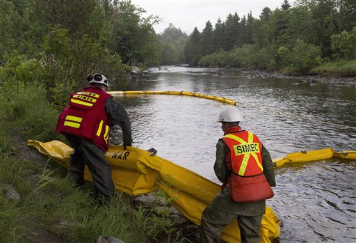 Workers lay booms on the Chaudiere River near Lac-Megantic, Quebec, to contain the crude oil spill following a train derailment and explosion.