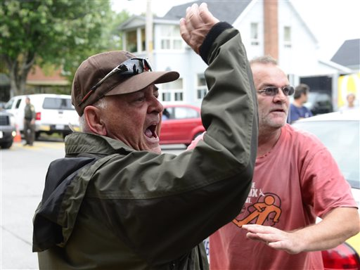 Angry citizens heckle Rail World Inc. President and CEO Edward Burkhardt as he tours Lac-Megantic, Quebec, on Wednesday.