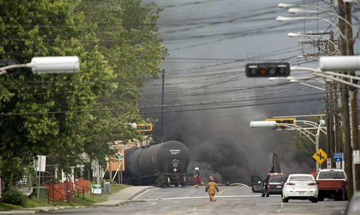 Smoke rises from derailed railway cars that were carrying crude oil in downtown Lac-Megantic, Quebec, on Saturday.