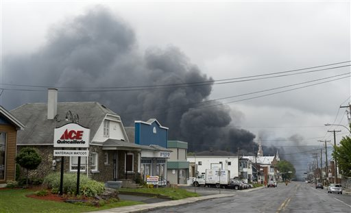 Smoke billows behind buildings in Lac-Megantic, Quebec, hours after a fiery train derailment Saturday.