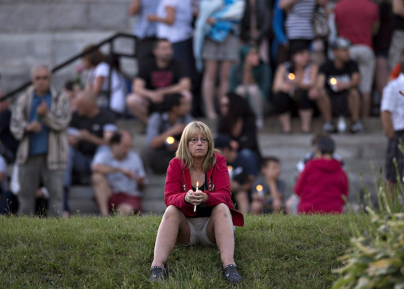 A women sits in front of the St-Agnes church during a vigil to the victims of the train crash in Lac-Megantic, Quebec, Friday, July 12, 2013. Transportation workers moved carefully Friday in and around the site of the nearly week-old derailment that incinerated the heart of this small Quebec town and killed 50 people, searching for evidence that would help explain what led to such massive destruction. (AP Photo/The Canadian Press, Jacques Boissinot) Canada;Quebec;Montreal;transportation;business;Canadian;economic;economy;industry;move;ship;shipping;transit;transport;travel industry;commerce;tourism;fire;train;rail;derail;tragedy;disaster