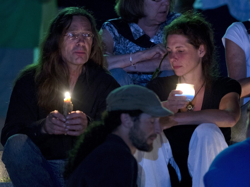People gather in front of the St-Agnes church during a vigil for the victims of the train crash in Lac-Megantic, Quebec, Friday, July 12, 2013. Transportation workers moved carefully Friday in and around the site of the nearly week-old derailment that incinerated the heart of this small Quebec town and killed 50 people, searching for evidence that would help explain what led to such massive destruction. (AP Photo/The Canadian Press, Jacques Boissinot) Canada;Quebec;Montreal;transportation;business;Canadian;economic;economy;industry;move;ship;shipping;transit;transport;travel industry;commerce;tourism;fire;train;rail;derail;tragedy;disaster