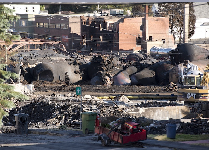 Charred tanker cars from the train crash scene remain in Lac-Megantic, Que., Friday, July 12, 2013. Transportation workers moved carefully Friday in and around the site of the nearly week-old derailment that incinerated the heart of this small Quebec town and killed 50 people, searching for evidence that would help explain what led to such massive destruction. (AP Photo/The Canadian Press, Jacques Boissinot) Canada;Quebec;Montreal;transportation;business;Canadian;economic;economy;industry;move;ship;shipping;transit;transport;travel industry;commerce;tourism;fire;train;rail;derail;tragedy;disaster