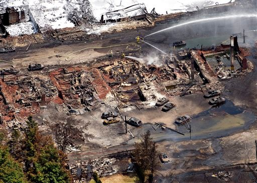 The downtown core lays in ruins as fire fighters continue to water smoldering rubble Sunday, July 7, 2013 in Lac Megantic, Quebec after a train derailed ignited tanker cars carrying crude oil. (AP Photo/The Canadian Press, Paul Chiasson)