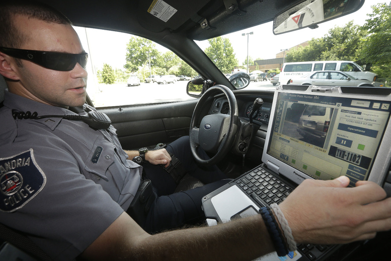 Officer Dennis Vafier of the Alexandria Police Department uses a laptop in his squad car to scan vehicle license plates during his patrols Tuesday in Alexandria, Va.