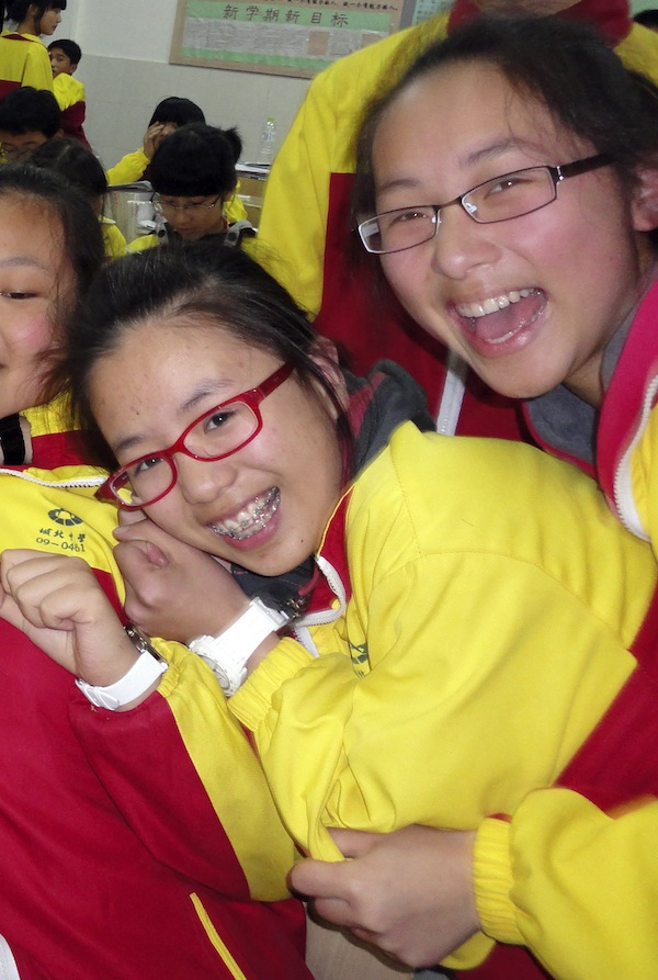 In this undated photo made available Monday, July 8, 2013, Ye Mengyuan, at left and Wang Linjia, right, pose for photos with other classmates in the classroom in Jiangshan city in eastern China's Zhejiang province. Chinese state media and Asiana Airlines have identified the two victims of the Asiana Airlines crash at San Francisco International Airport girls as Ye Mengyuan and Wang Linjia, students in Zhejiang, an affluent coastal province in eastern China. (AP Photo)