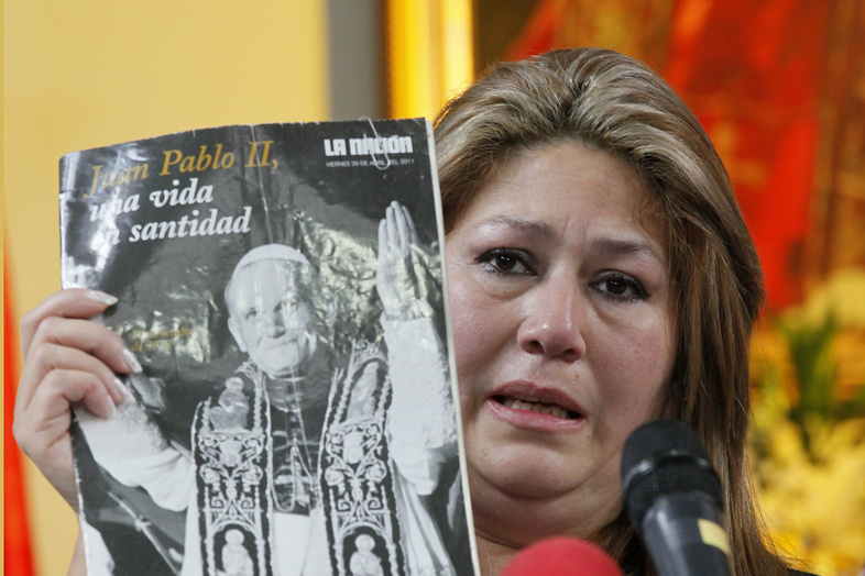 Floribeth Mora of Costa Rica holds up a magazine featuring Pope John Paul II on the cover as she gives her account of a miracle attributed to the late pope, during a news conference in San Jose, Costa Rica, on Friday.