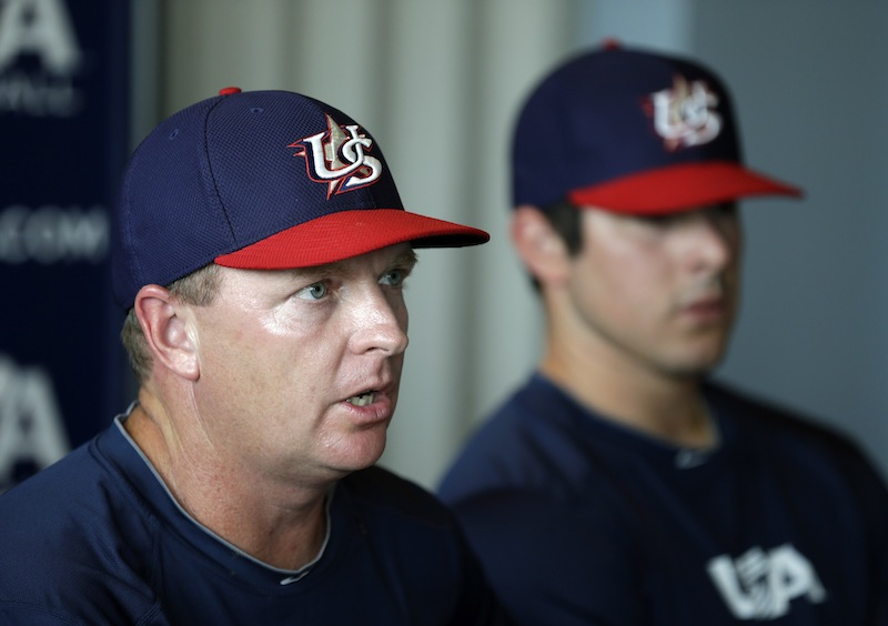 USA manager Jim Schlossnagle speaks during a news conference as pitcher Carlos Rodon, right, looks on, Wednesday, July 17, 2013, in Des Moines, Iowa. The Cuban national team and a squad made up of American college stars will square off in a five-game, three-city series starting Thursday in Des Moines. (AP Photo/Charlie Neibergall)