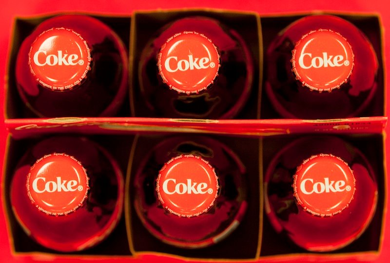 In this Monday, July 15, 2013 photo, bottle tops of Coca-Cola 8 oz. bottles are shown in Doral, Fla. The Coca-Cola Co. reports quarterly financial results before the market opens on Tuesday, July 16, 2013. (AP Photo/Wilfredo Lee)