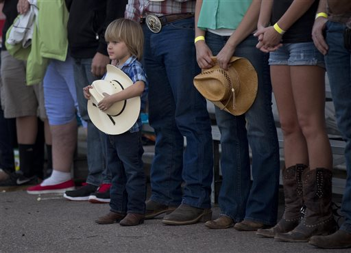 A young boy holds his hat as he and others stand for the national anthem before the start of the Prescott Frontier Days Rodeo, Wednesday in Prescott, Ariz. A mile-high city about 90 miles northwest of Phoenix, Prescott remains a modern-day outpost of the pioneer spirit. It's that spirit that will guide officials as they navigate the days ahead and figure out how to honor the elite Hotshot firefighters who died in a nearby wind-driven wildfire that is still burning. (AP Photo/Julie Jacobson)