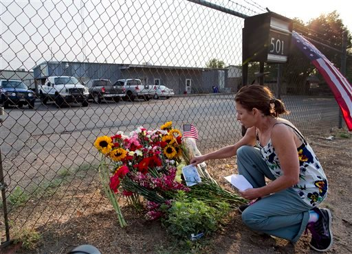 Toby Schultz lays flowers at the gate of the Granite Mountain Hot Shot Crew fire station, Monday in Prescott, Ariz. An out-of-control blaze overtook the elite group of firefighters trained to battle the fiercest wildfires, killing 19 members as they tried to protect themselves from the flames under fire-resistant shields.
